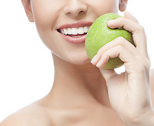 Close up of a smiling woman with a green apple